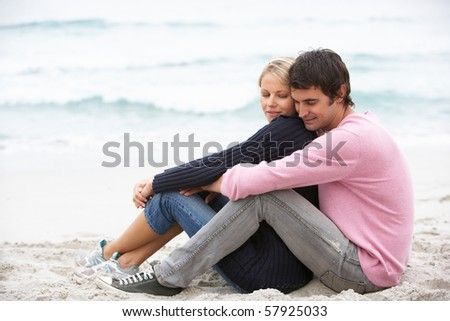 Young Couple On Holiday Sitting On Winter Beach