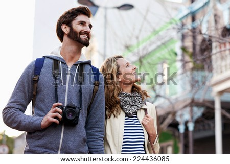 young couple on holiday walking with camera in city having fun vacation in autumn - stock photo