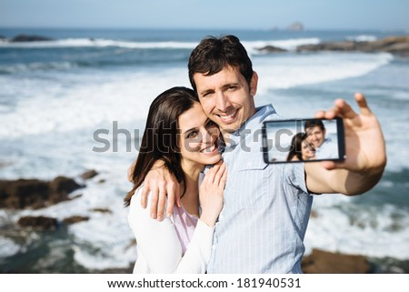 Young couple on honeymoon travel in Asturias coast, Spain, taking selfie portrait photo with smartphone camera. - stock photo