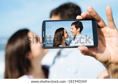 Young couple on honeymoon travel taking selfie portrait photo with smartphone camera. - stock photo