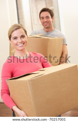 Young couple on moving day carrying cardboard boxes - stock photo