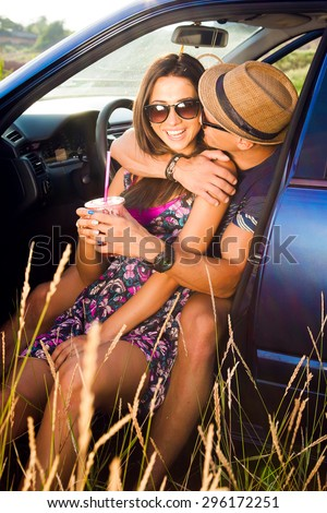 Young couple on road trip. Young couple sitting on the hood of their car with man answering a phone call and woman sitting by.Car is parked alongside coastal seashore with bright sunlight.sunshine day - stock photo