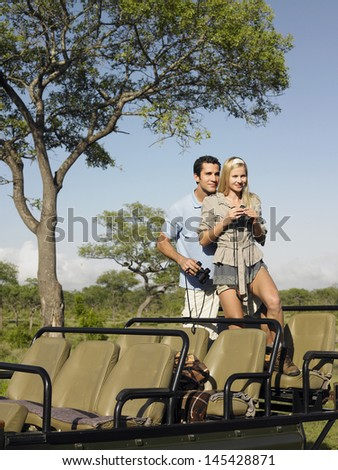 Young couple on safari standing in jeep and with binoculars - stock photo