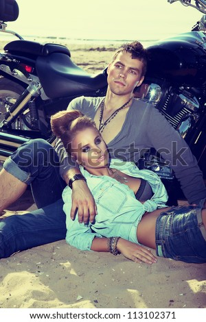 Young couple on sand of beach relaxing over background of a beautiful bike. Adventure and vacations concept - stock photo