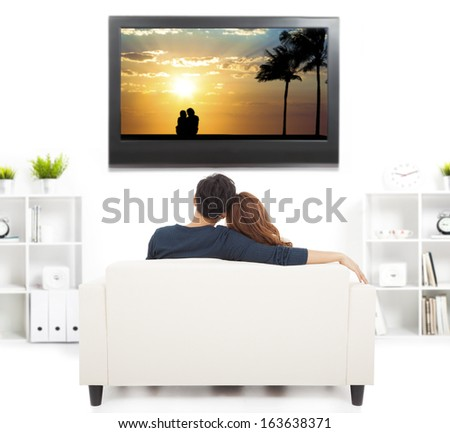 young couple on sofa watching TV - stock photo