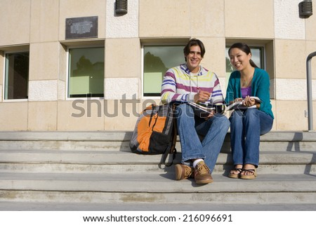 Young couple on steps studying, smiling, portrait, low angle view - stock photo