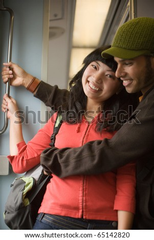 Young couple on subway train - stock photo