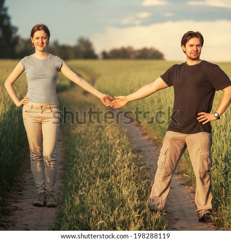 Young couple on summer field. - stock photo