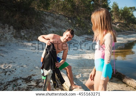 Young couple on the beach dressing up for the pabble boarding. Front view closeup - concept of harmony with the nature, free and healthy living, freelance, remote business. - stock photo