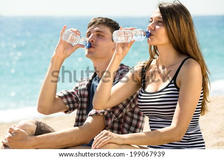 Young couple on the beach drinking fresh water on a hot summer day - stock photo