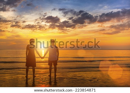 Young couple on the beach during amazing sunset. Honeymoon. - stock photo