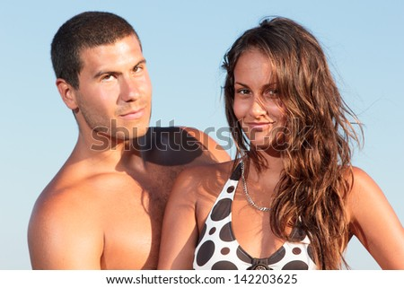 Young couple on the beach in the summertime - stock photo