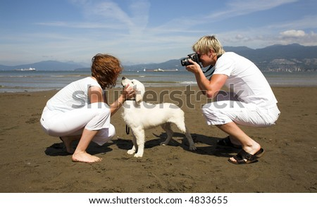 young couple on the beach with dog in taking pictures - stock photo