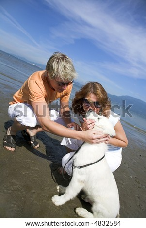 young couple on the beach with dog in vancouver