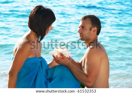Young couple on the beach with seashell - stock photo