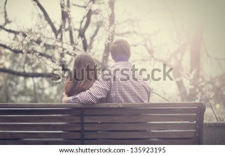 Young couple on the bench at the street. - stock photo