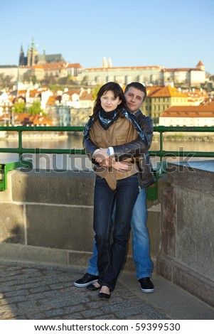 young couple on the Charles Bridge on the skyline - stock photo