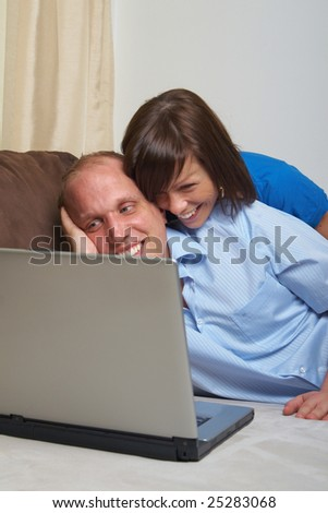 Young couple on the couch at home looking at the laptop!