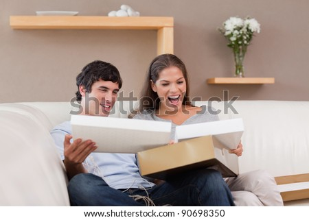 Young couple on the couch opening parcel - stock photo