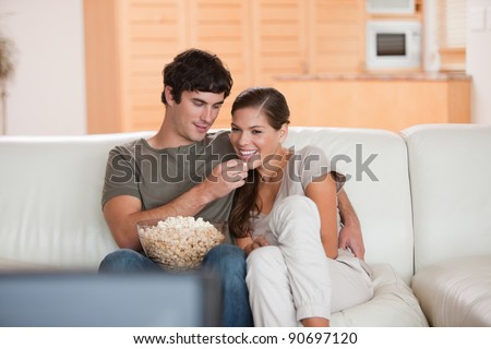Young couple on the couch watching a movie together - stock photo