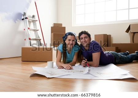 Young couple on the floor, making projects about their new home