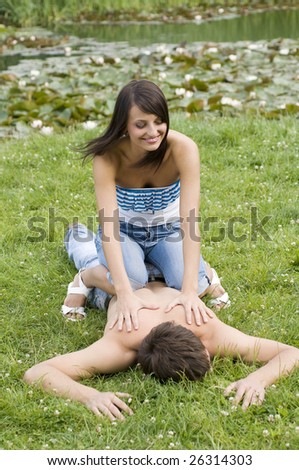 young couple on the grass in the park the girl doing massage - stock photo