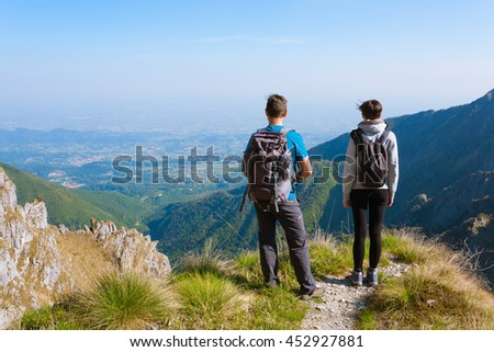 Young couple on top of mountain looking at the horizon. Mountain panorama