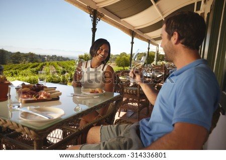 Young couple on vacation drinking wine in a restaurant. Man and woman in a wine bar restaurant by a vineyard. - stock photo