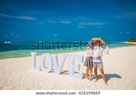 Young Couple on vacation, honeymoon, taking picture on the sandy beach
