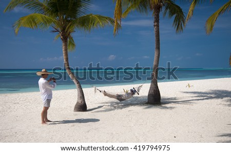 young couple on vacation in Kuredu, Maldives, here ejoying sandy beach  palm trees and hammock - stock photo