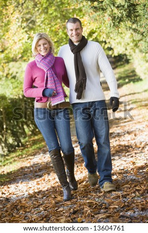 Young couple on walk through autumn woods - stock photo