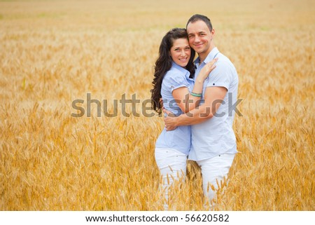 Young couple on wheat field - stock photo