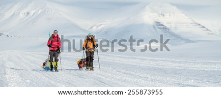 young couple on winter expedition in wilderness mountainous landscape - panoramic view - stock photo