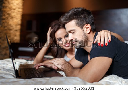 Young couple online shopping on bed by laptop, woman embrace man shoulder - stock photo