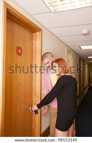 Young couple opening hotel room door. - stock photo