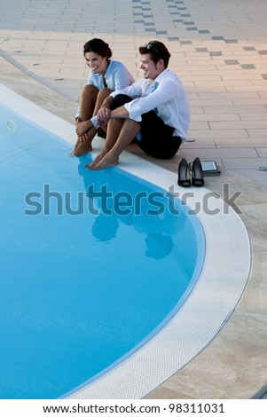 Young couple or businsspeople relaxing by pool