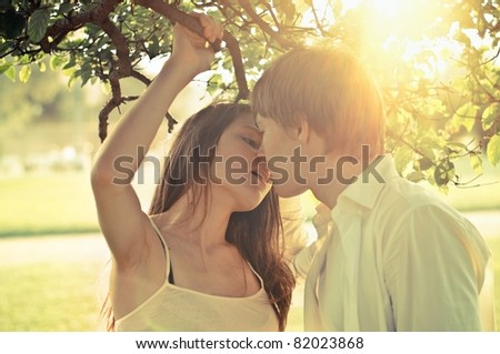 Young couple outdoors, focus on girl's face, shallow DOF - stock photo