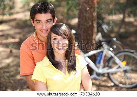 Young couple outdoors with bicycles - stock photo