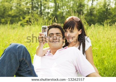 Young couple outdoors, woman taking photo with mobile phone - stock photo