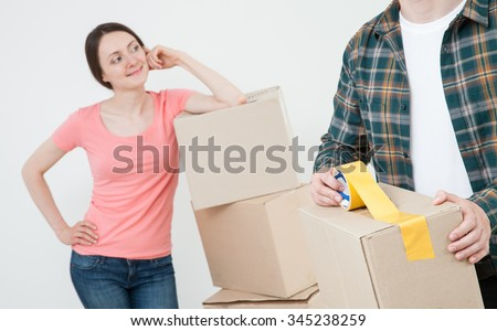 Young couple packing their things in cardboard boxes, neutral background - stock photo