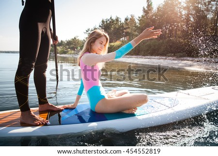 Young couple paddling on sup board with paddle. Closeup, side view, focus on woman - concept of harmony with the nature, free and healthy living, freelance, remote business. - stock photo