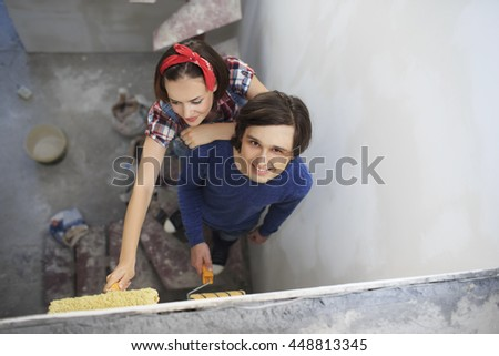 Young couple painting the flat. Young woman and a man with rollers in them hands preparing to paint the wall.   - stock photo