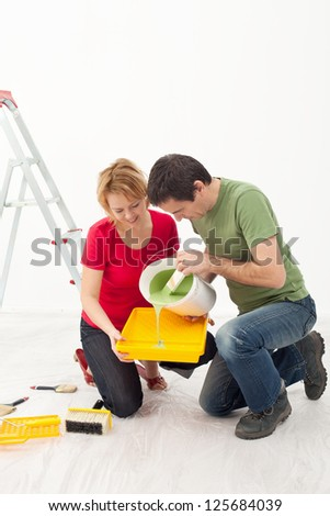 Young couple painting their home - pouring the paint - stock photo
