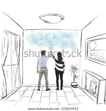 Young couple painting together the walls of house - stock photo