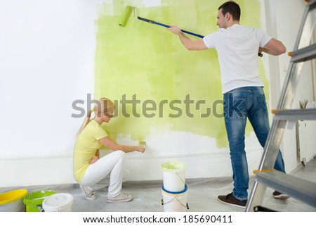 Young couple painting wall in their room - stock photo