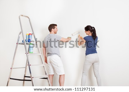 Young couple painting wall together at home