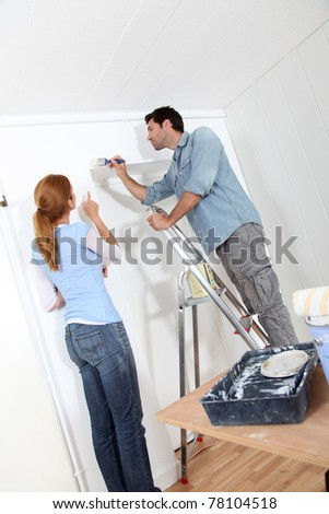 Young couple painting walls of their new house