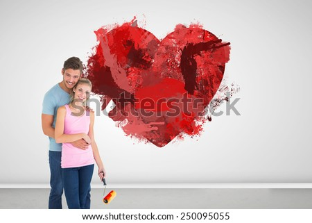 Young couple painting with roller against grey room - stock photo