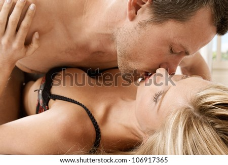 Young couple passionately kissing in bed.