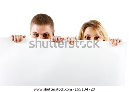 Young couple peeking out from behind the booth - stock photo